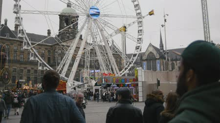 hármas : AMSTERDAM, NETHERLANDS - 16 oct 2016, Dam Square - historical center of Holland CAPITAL, tourists, bicycle and cars on the street, View with amusement Park - Ferris wheel, telephoto