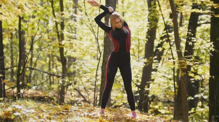 tilts : Woman doing fitness exercises outdoor. Female stretching her elbows in autumn forest. Slim girl at outdoor workout