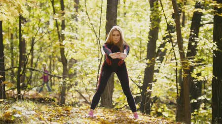 tilts : Woman doing fitness exercises outdoor. Female stretching her loin in autumn forest. Slim girl at outdoor workout