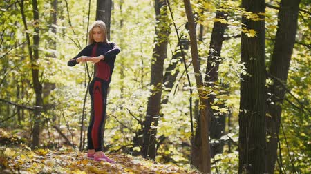 tilts : Woman doing fitness exercises outdoor. Female stretching in autumn forest. Slim girl at outdoor workout, slow-motion