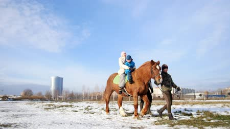 learning to walk : Hippotherapy for kid with cerebral palsy syndrome at winter cold day - contact kids therapy and rehabilitation horse-riding club - on the background of the city Stock Footage