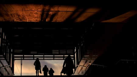 impersonal : People get out from subway at winter sunset, silhouette