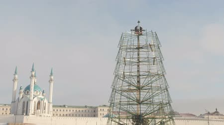 достигать : 1 DECEMBER 2016, KAZAN, RUSSIA, making construction for happy new year - two workers in truck with mobile crane for installation of metal tree, wide angle. Mosque Kul-Sharif Стоковые видеозаписи