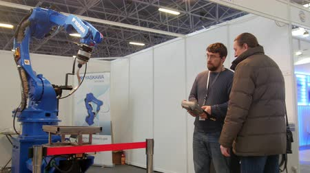 spawacz : KAZAN, RUSSIA, 9 DECEMBER 2016, 15th International Specialised Exhibition. Mechanical Engineering. Metalworking. 10th International Exhibition. Technowelding. two man looking on robo arm for welding