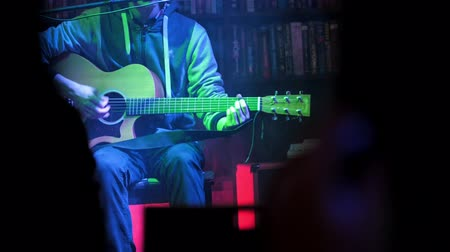 barmetro : Guitarist plays acoustic guitar in night club, close up