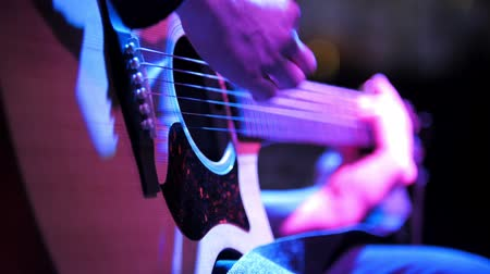 barmetro : Musician in night club - guitarist plays blues acoustic guitar, extremely close up
