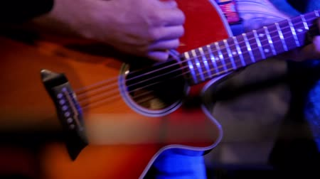 akusztikus : Musician at rock concert - guitarists plays red acoustic guitar in night club, close up