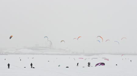 adrenalin : Winter extremal sport - a different colorful snow-kites over the ice river in front of city at blizzard cloudy day