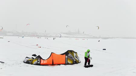 kiting : Kazan, Russia, 7 january 2017, Snow-kite festival orange wind, athletes ready for competition ice river over the city Stock Footage