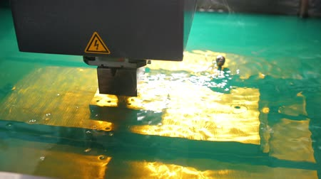 tryska : Cutting of sheet metal process in water. Sparks fly from laser by automatic factory, production, front view
