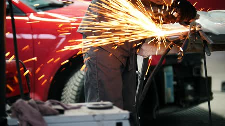 metal worker : Car auto service - worker grinding metal construction with a circular saw