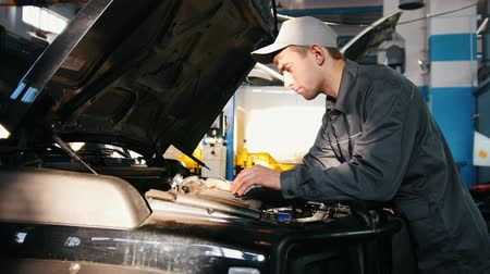 toolbox : Mechanic male in automobile garage processing engine diagnostic - checking in hood of the car for luxury SUV