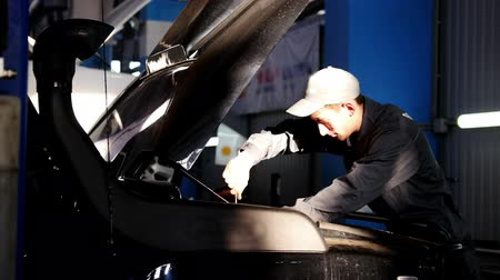 İngiliz anahtarı : Mechanic male unscrews with a screwdriver in hood of the car for SUV