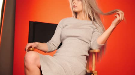 feminity : Blonde model girl in photo studio sitting on chair - fashion backstage