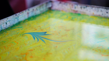 marbling : Liquid Ebru art technics - drawing brush create a picture on water - blue figure on yellow background