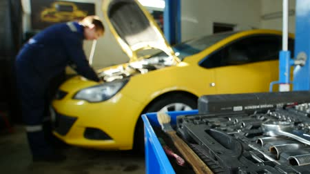 diagnostics : Mechanic works in professional auto service near repairs yellow car, time-lapse Stock Footage
