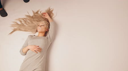 feminity : Blonde model girl lying in photo studio - photographer take a photo, fashion backstage