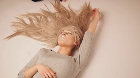 feminity : Blonde model girl lying in photo studio - photographer combing the hair of the model, top view