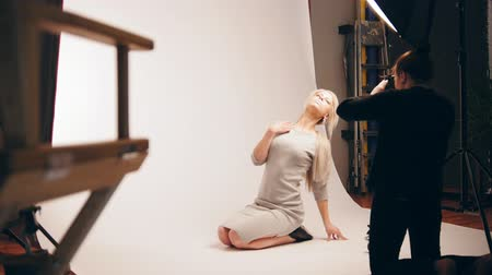feminity : Fashion photo backstage - Blonde handsome girl posing for photographer - model sits at knees