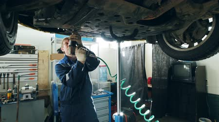 toolbox : Garage auto service - mechanic unscrewing the bottom of the lifted car, small business