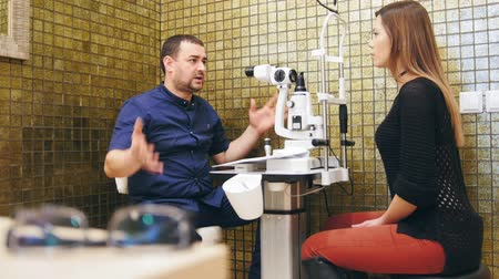 sighted : Ophthalmology concept - the doctor explains to the woman patient his vision in optometrists room Stock Footage