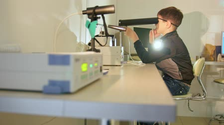 soczewki kontaktowe : Ophthalmology clinic - child checks eyes vision with high technology device