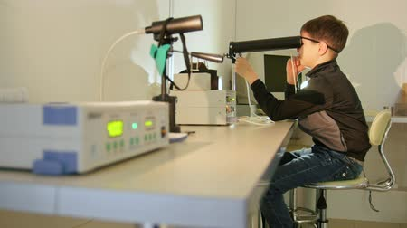 soczewki kontaktowe : Ophthalmology clinic - teenager checks eyesight with high technology device