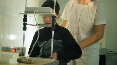 soczewki kontaktowe : Ophthalmology clinic - teenager boy checks eyes vision with high technology device