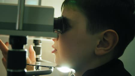 astigmatism : Slider view of child teenager checks eyes vision with high technology device Stock Footage