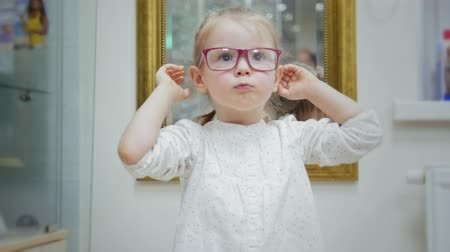 eski moda : Little girl tries glasses near mirror - shopping in ophthalmology clinic