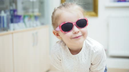 perforation : little girl playing and Hamming in front of a mirror and tries fashion medical glasses near mirror - shopping in ophthalmology clinic