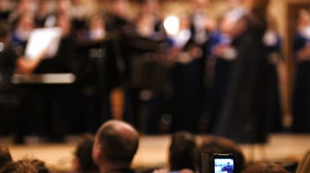 choral : Audience in concert hall - people shooting performance on smartphone, music opera