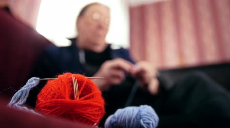 starość : De-focused view of old woman sits on the sofa and knits wool socks - pensioners at home