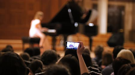 choral : Audience in concert hall during performing piano girl- people shooting performance on smartphone, music opera