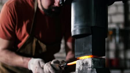 zanaat : Man blacksmith in workshop forging red hot iron on anvil - small business Stok Video