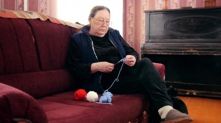 starość : Old woman pensioner home - knits wool socks sitting on the sofa - elderly lady hobby Wideo