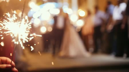 июль : Sparkler in hands on a wedding - bride, groom and guests holding lights in, defocused and slow-motion