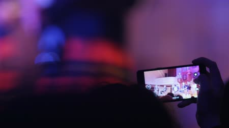 choral : Spectators at concert shooting video performance on smartphone, scottish musicians