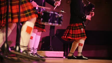 felvidéki : Traditional scottish band musicians in white socks and kilts singing with bagpipes on the stage Stock mozgókép
