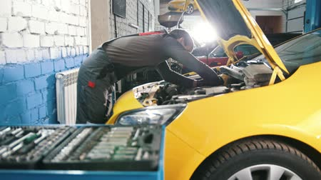 toolbox : A mechanic checks the electrical in the hood of the car- repairing in engine compartment