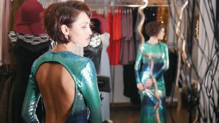 drápy : Pretty red haired female in green evening dress posing for photographer in clothing store boutique Dostupné videozáznamy