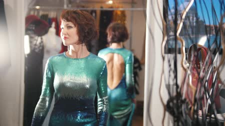 drápy : Pretty red haired female in green evening dress posing in mirror in boutique showroom