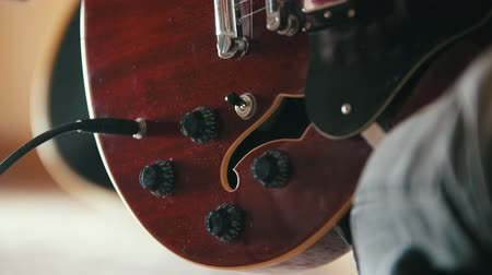 headstock : Musician disables guitar after a performance, hands close up