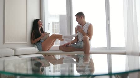 sitting room : Young happy couple sitting on the windowsill, laughing, flirting, plauing