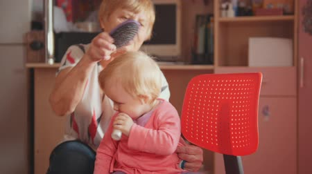 nipple : Grandmother with her cute granddaughter, talking, smiling and combing