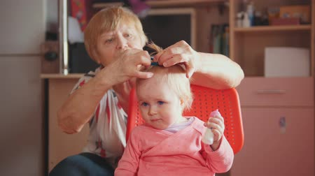 nipple : Grandmother with her cute whimper granddaughter, talking and combing Stock Footage