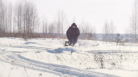 portátil : Adult man in winter clothing fast riding and jumping on a mini snowmobile through the deep snow, stalled towing vehicle