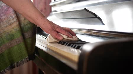 old maid : Old woman at home wipes the dust on piano