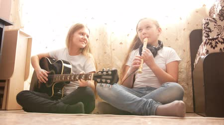 otthonos : Two female teens playing musical instruments at home Stock mozgókép