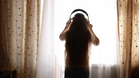 contornos : Silhouette of teenager girl in headphones in front of the window